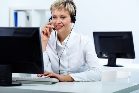 Young secretary with headset answering a call Stock Photo - 11809472