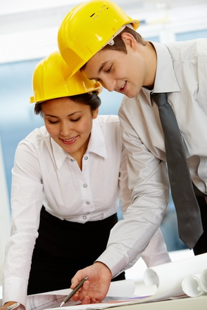 Portrait of two architects in helmets discussing document at meeting Stock Photo - 11809518