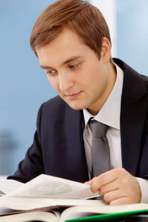 Portrait of thinking businessman reading book  photo