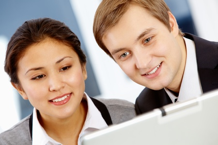 interested: Successful colleagues looking at laptop monitor with smiles during work Stock Photo