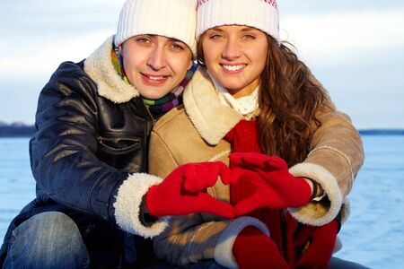 winterwear: Portrait of happy couple in warm clothes making heart by hands