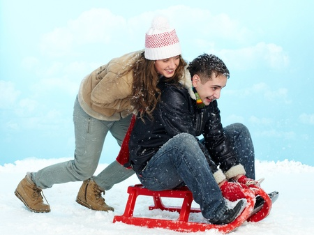Portrait of happy couple tobogganing during winter vacation photo