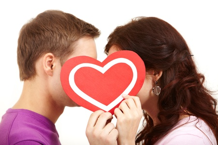 Two young people kissing behind a paper heart  photo