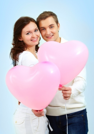 adult valentine: Portrait of two young people holding heart-shaped balloons