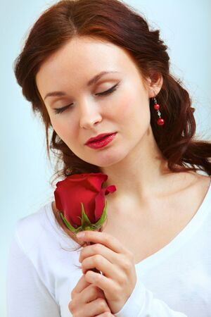 Portrait of attractive woman holding red rose and smelling it photo