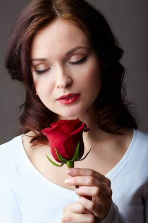 Portrait of attractive woman holding red rose and enjoying its smell photo