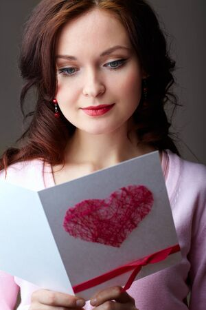 Portrait of young woman holding Valentine card and reading it photo