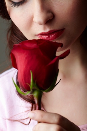 Close-up of attractive woman holding red rose and enjoying its smell photo