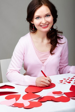 Portrait of happy woman signing valentine cards  photo