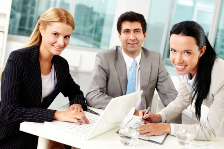 Three business people looking at camera during work in office  Stock Photo - 11920915