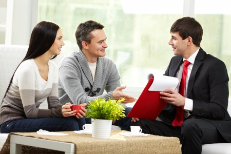 financial insurance: Portrait of modern couple listening to manager explanation about conditions of mortgage