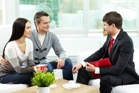 seated: Portrait of modern couple listening to manager explanation about conditions of mortgage