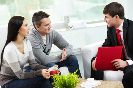 financial insurance: Portrait of modern couple talking to manager while discussing conditions of mortgage