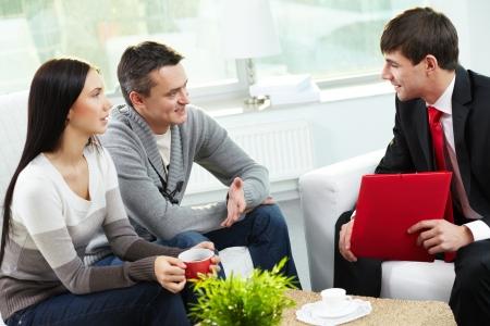 Portret van de moderne echtpaar in gesprek met manager bij de discussie over de voorwaarden van de hypotheek Stockfoto