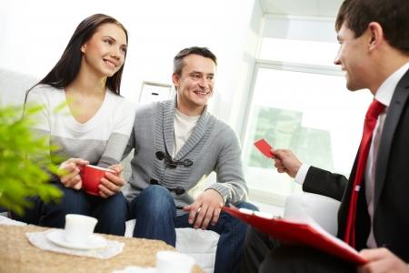 реальный: Портрет современного пары, глядя на агента по недвижимости давая свою визитную карточку