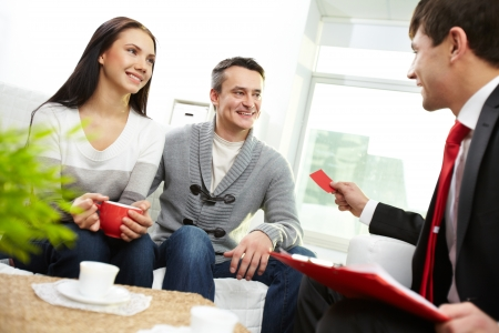 financial insurance: Portrait of modern couple looking at real estate agent giving his visiting card  Stock Photo