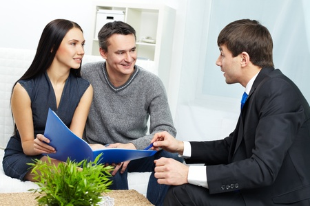 Portrait of modern couple listening to manager explanation about conditions of mortgage  photo