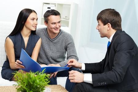 Portret van moderne paar te luisteren naar de manager van uitleg over de voorwaarden van de hypotheek