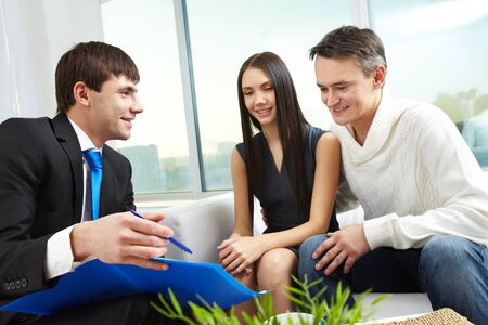 Portrait of modern couple listening to manager explanation of mortgage conditions  photo