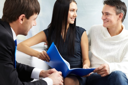 real estate business: Portrait of modern couple discussing mortgage conditions with real estate agent near by