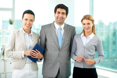 Three business people in formalwear looking at camera in office  Stock Photo - 11920737