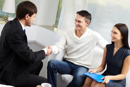 happy client: Portrait of modern couple making a deal with real estate manager Stock Photo