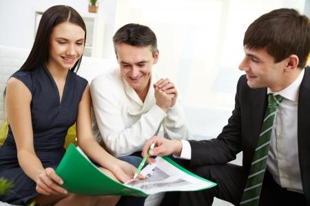 Portret van moderne paar te luisteren naar de manager van uitleg van de hypothecaire voorwaarden Stockfoto