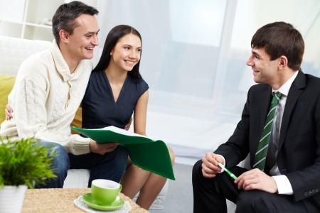 Portrait of modern couple and real estate manager discussing mortgage conditions  Stock Photo