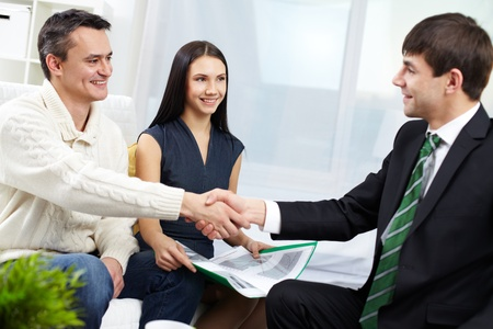 handshaking: Portrait of modern couple making a deal with real estate manager Stock Photo