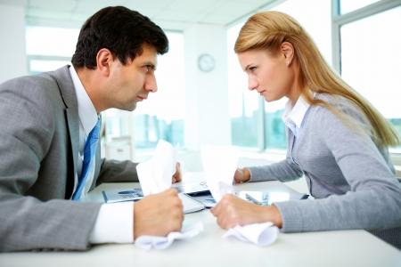 desacuerdo: Los perfiles de los empleados enojados con papeles mirándose unos a otros estrictamente