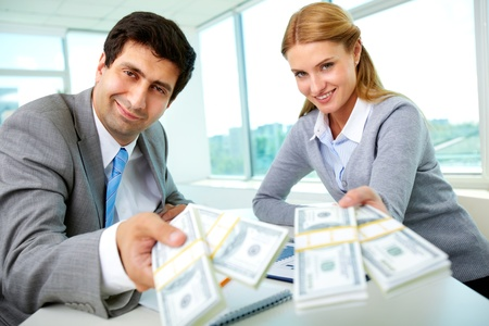 loans: Two business partners at workplace giving money and looking at you Stock Photo