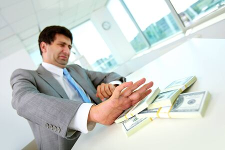 corruption: Image of disgusted male employee moving dollar bills away and refusing to take bribe Stock Photo
