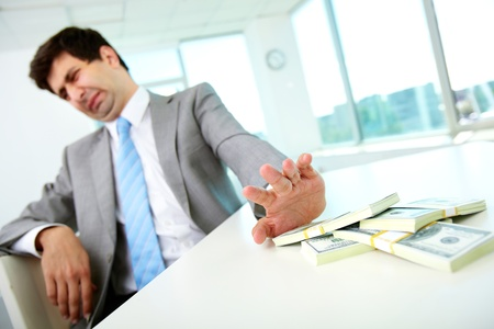 corrupcion: Imagen de sexo masculino de disgusto moviendo billetes de un d�lar de distancia y se niega a tomar soborno