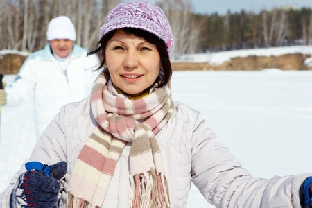 Portrait of attractive middle woman looking at camera while skiing outside photo