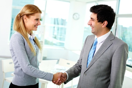 handshaking: Portrait of happy business partners shaking hands at meeting