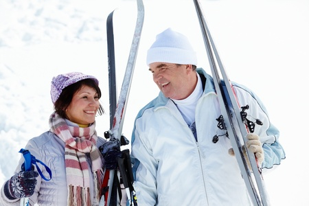 both: Portrait of mature couple with skis outside