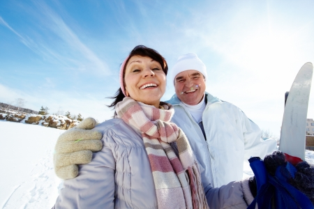 active seniors: Portrait of mature couple with skis outside
