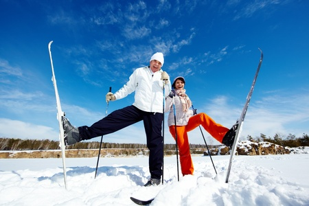 Portrait of happy mature couple posing in front of camera while skiing photo