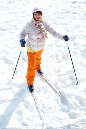 Portrait of attractive middle aged woman looking at camera while skiing outside photo