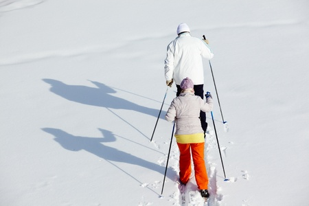 Rear view of mature couple skiing in winter park photo
