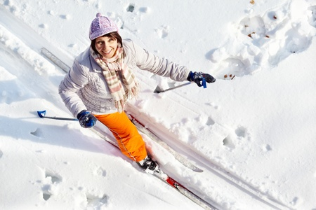 Above angle of middle aged woman skiing outside photo