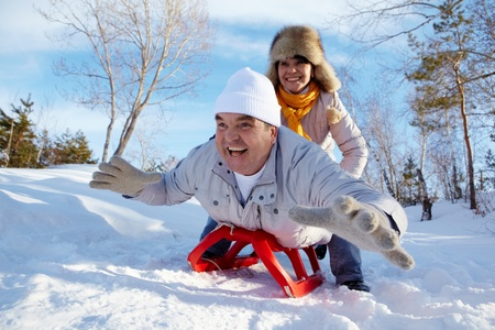 sledge: Retrato de pareja madura feliz de montar en el trineo en invierno