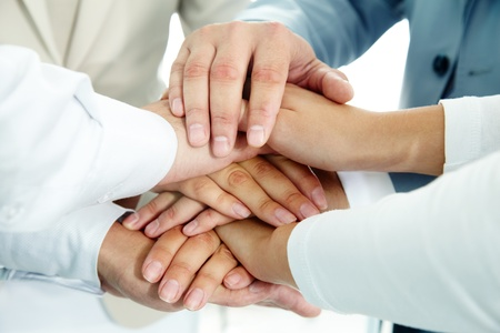 team victory: Image of businesspeople hands on top of each other as symbol of their partnership