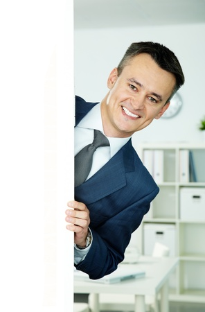 Portrait of smiling businessman peeking out of blank billboard photo