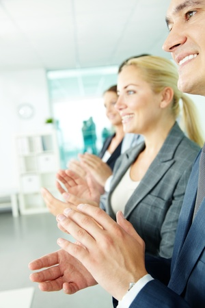 ovation: Photo of business partners applauding with happy man in front Stock Photo
