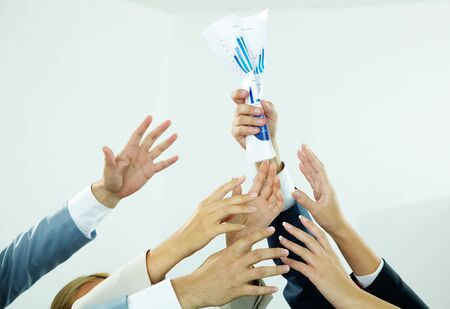 Image of several human hands trying to get crampled paper from male hand