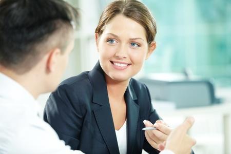 Un gerente de una mujer mirando socio de negocios durante la conversación