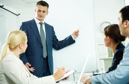 A business man and his partners discussing something on a whiteboard Stock Photo - 11919523