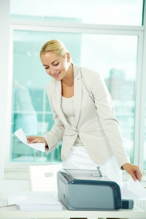 A beautiful businesswoman printing documents in office Stock Photo - 11919566