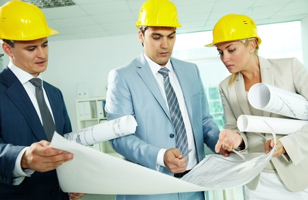 Portrait of three architects in helmets discussing blueprint photo